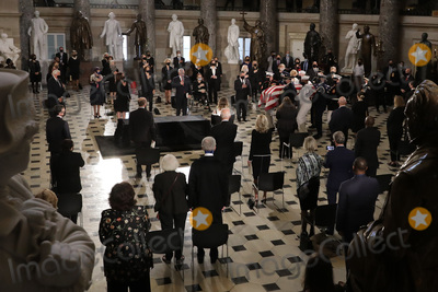 Photo - Spaced apart and wearing masks to reduce the risk posed by the coronavirus members of Congress guests and family members stand as US Supreme Court Associate Justice Ruth Bader Ginsburg is brought into Statuary Hall at the US Capitol on September 25 2020 in Washington DC Ginsburg who was appointed by former US President Bill Clinton served on the high court from 1993 until her death on September 18 2020 She is the first woman to lie in state at the Capitol Credit Chip Somodevilla  Pool via CNPAdMedia