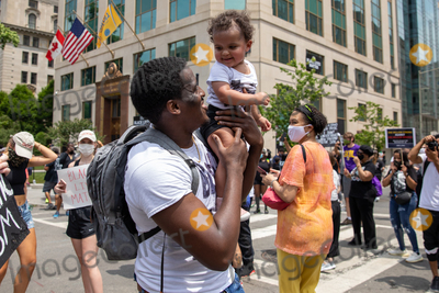 Photo - Nyron Dancy holds up his 1-year-old daughter Nyomi Dancy during a march against police brutality and racism in Washington DC on Saturday June 6 2020Credit Amanda Andrade-Rhoades  CNPAdMedia
