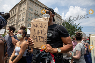 Photo - Justin Bonhomme holds up a Black Lives Matter sign near the White House during a march against police brutality and racism in Washington DC on Saturday June 6 2020Credit Amanda Andrade-Rhoades  CNPAdMedia