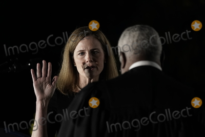 CLARENCE THOMAS Photo - Associate Justice of the Supreme Court Clarence Thomas administers the oath of office to Judge Amy Coney Barrett to be Associate Justice of the Supreme Court on the South Lawn of the White House in Washington DC on Monday October 26 2020  US President Donald J Trump and her husband Jesse M Barrett look onCredit Ken Cedeno  Pool via CNPAdMedia