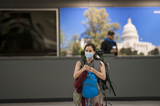 The Interns Photo - A woman wears a protective mask as she and other passengers arrive from Dubai after a 14-hour flight on Emirates flight 231 at the international terminal at Dulles International Airport in Dulles Va Monday March16 2020 Some people are taking the precaution of wearing face masks as they arrive to be greeted by family and or friends Credit Rod Lamkey  CNPAdMedia