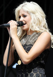 Adored Photo - British pop singer Pixie Lott performs live on the V Stage during day two of the 15th annual V Festival 2010 held at Hylands Park  The 19-year-old Turn It Up singer went for a retro look in a sixties inspired gold and black patterned mini dress with sexy gold garters and thigh high nylons and backstage Pixie accessorized with a large floppy hat  While on stage Pixie who also wore a large JAdore multi-finger ring stopped between songs to tell the festival goers that her feet hurt and she took off her cool studded high heel boots  Essex UK 082210