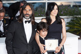 The Jury Photo - CANNES FRANCE - MAY 19 (L-R) Director Nadine Labaki actor Zain Alrafeea and Composer Khaled Mouzanar pose with the Jury Prize award for Capharnaum at the Palme DOr Winner Photocall during the 71st annual Cannes Film Festival at Palais des Festivals on May 19 2018 in Cannes France(Photo by Laurent KoffelImageCollectcom)